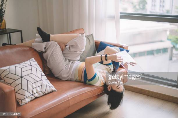 an asian chinese female university student communicating with her friend at home using her transparent digital tablet lying on sofa - surfing the net stock pictures, royalty-free photos & images