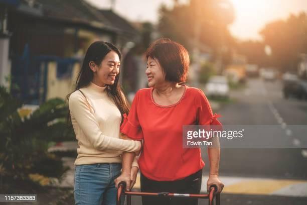 彼女の歩行援助を回復し、彼女の娘によって助けられて歩くアジアの中国人女性 - 杖 ストックフォトと画像