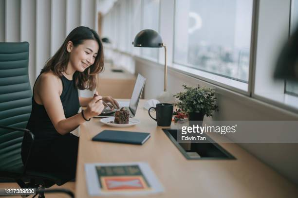 an asian chinese female white collar worker young executive enjoying her chocholate cake while working at her workstation in co-sharing working office in the afternoon with social distancing applied - surfing the net stock pictures, royalty-free photos & images