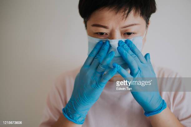 an asian chinese female with her latex surgical glove wearing her face mask before going out - nose mask stock pictures, royalty-free photos & images