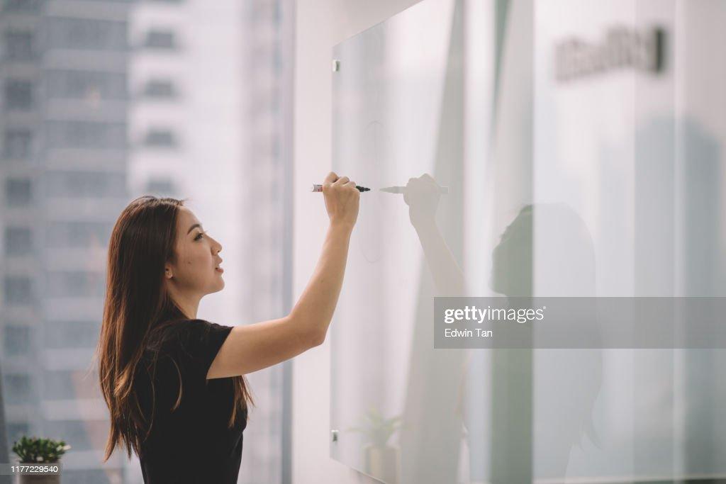 una donna cinese asiatica che scrive su lavagna bianca con la pennarello durante la riunione della conferenza nella sala conferenze dell'ufficio : Foto stock