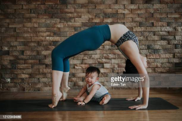 an asian chinese female yoga instructor with bridge pose while her son looking at camera