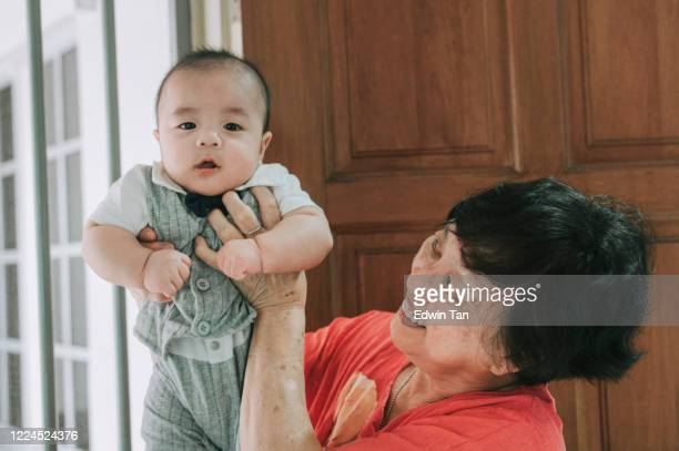 an asian chinese grandmother carrying her grandson baby boy at  her house