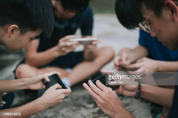 um grupo chinês asiático de adolescentes jogando jogo móvel na quadra de basquete após a escola usando geração de telefone z - rodada da competição - fotografias e filmes do acervo