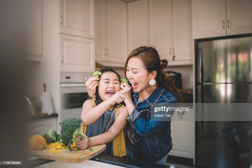 An Asian Chinese housewife having bonding time with her daughter in kitchen preparing food : Stock Photo