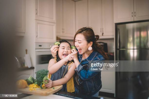 an asian chinese housewife having bonding time with her daughter in kitchen preparing food - asian stock pictures, royalty-free photos & images