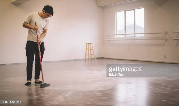an asian chinese male dancer cleaning up ballet dancer floor sweeping after practise with broom - sweeping stock pictures, royalty-free photos & images