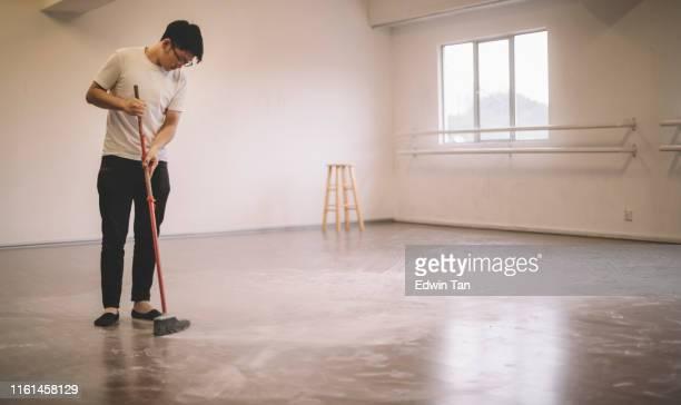 ほうきで練習した後にバレエダンサーの床を掃除するアジアの中国人男性ダンサー - 掃く ストックフォトと画像