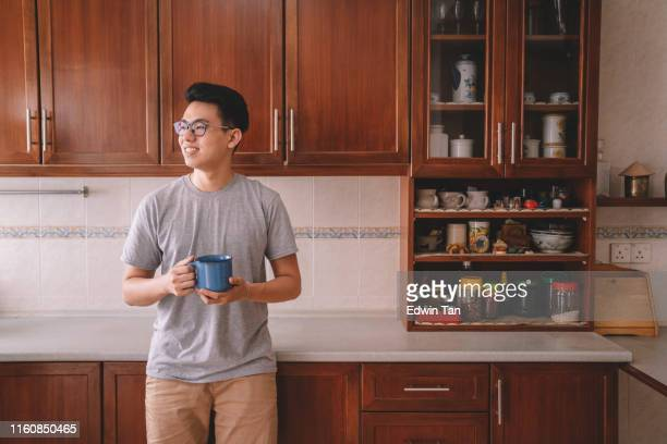 an asian chinese male having a cup of coffee in his kitchen in the morning before going to work - atividades de fim de semana imagens e fotografias de stock