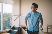 an asian chinese male patient recovering from his leg injury and walking with crutches in the hospital