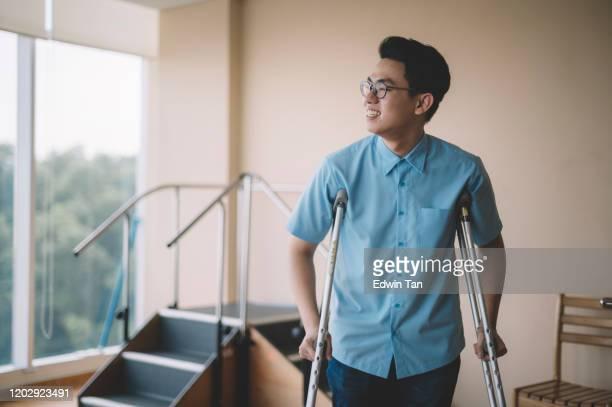 足の怪我から回復し、病院で松葉杖で歩いているアジアの中国人男性患者 - 杖 ストックフォトと画像