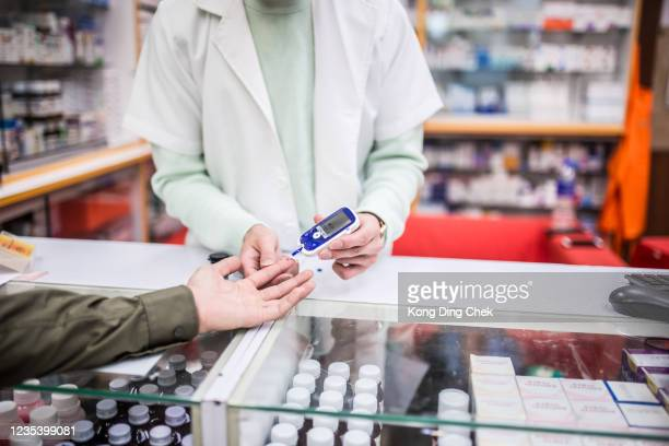 an asian chinese male pharmacist helping customer doing blood sugar test at pharmacy counter - glycemia stock pictures, royalty-free photos & images