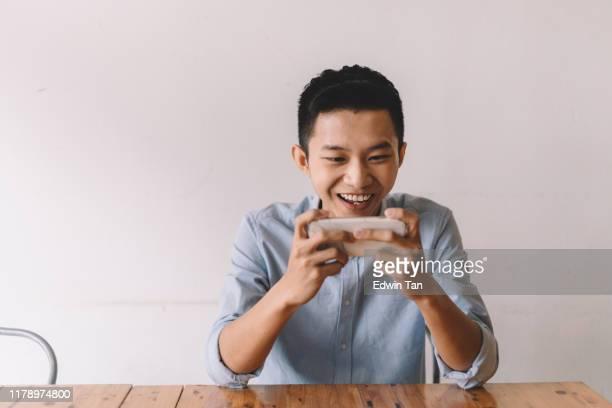昼休みの間にカフェでオンラインゲームをしているアジアの中国人男性 - ゲーム ストックフォトと画像