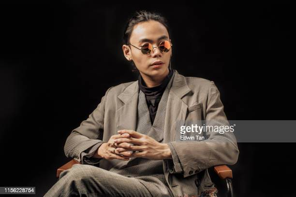 an asian chinese male studio portrait sitting on the chair with sunglasses looking away - handsome chinese men stock pictures, royalty-free photos & images