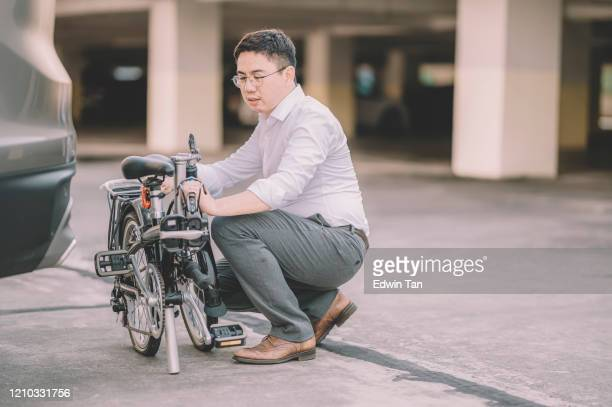 an asian chinese male white collar worker getting ready to work with his folding bicycle as transport commuting - foldable stock pictures, royalty-free photos & images