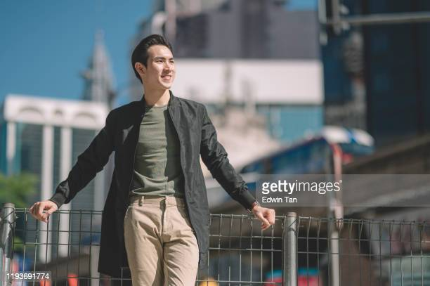 un cinese asiatico appoggiato alla recinzione della passerella pedonale in città durante il giorno con abbigliamento casual e giacca - casual chic foto e immagini stock