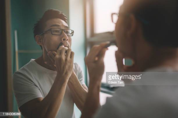 an asian chinese man shaving and getting ready to work in the morning - shaving stock pictures, royalty-free photos & images