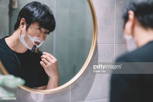 an asian chinese man shaving in the washroom in front of the mirror