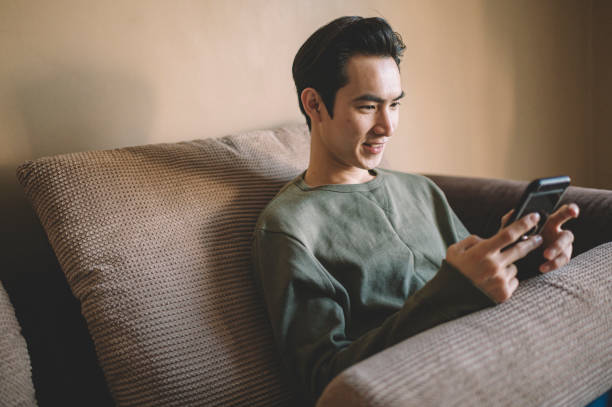 an asian chinese man sitting on his sofa with cushion relaxing with his smart phone surfing the net and shopping online - asian man using a cellphone stock pictures, royalty-free photos & images