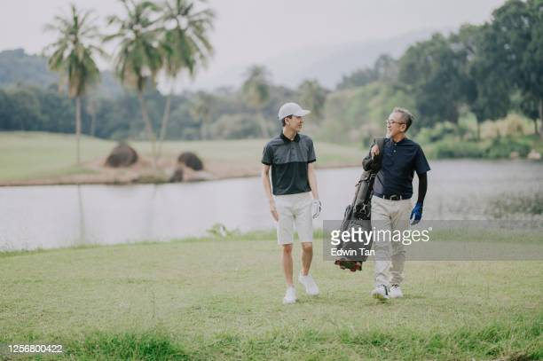 an asian chinese man with his teenager son walking toward golf course for the game carrying golf bag looking at view - early retirement stock pictures, royalty-free photos & images