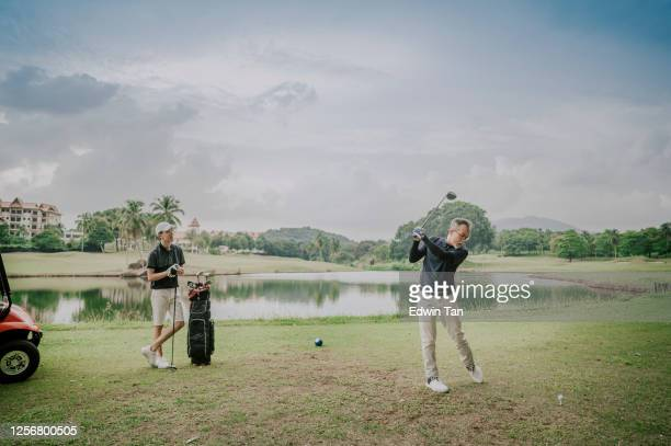 an asian chinese mature guy tee off swing his driver club at tee off point golf course in weekend while his son watching