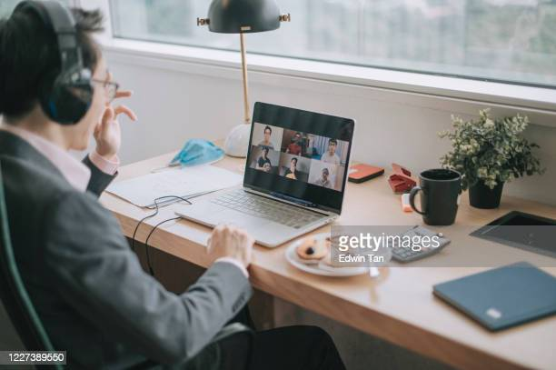 an asian chinese mid adult businessman having video conference with his colleague and business partners  in the office using headset and laptop - new normal stock pictures, royalty-free photos & images