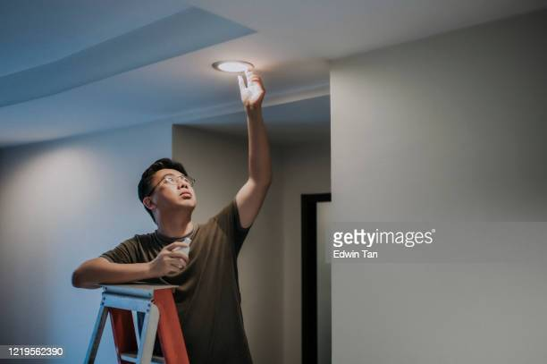 an asian chinese mid adult male changing light bulb in living room, apartment home - led light stock pictures, royalty-free photos & images