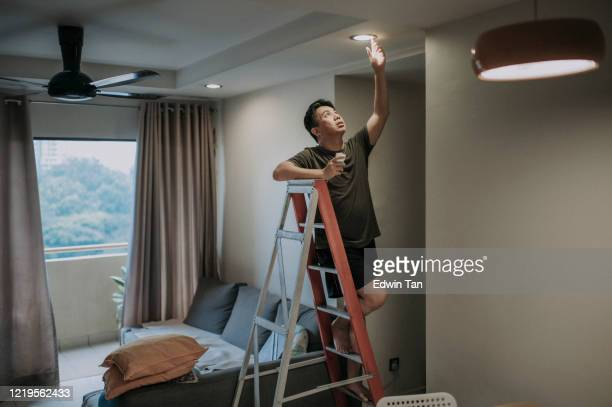 an asian chinese mid adult male changing light bulb in living room, apartment home - illuminated stock pictures, royalty-free photos & images