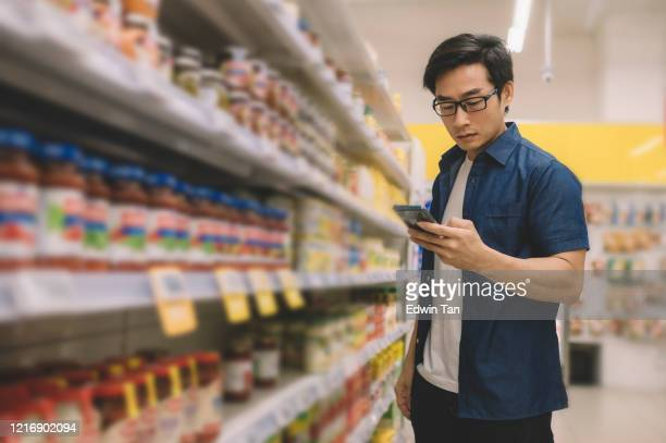 an asian chinese mid adult man buying groceries in supermarket on behalf of his wife and checking shopping list with his wife communicating through his mobile phone with internet - phone message stock pictures, royalty-free photos & images