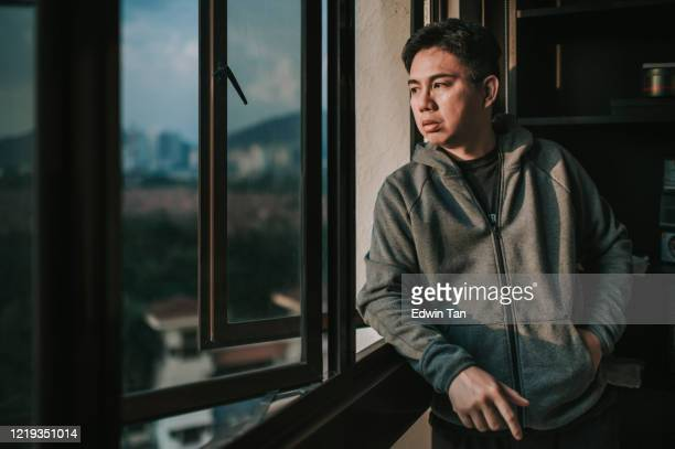 an asian chinese mid adult man looking outside of window from his home during sunset with serious facial expression with hooded shirt - hopelessness stock pictures, royalty-free photos & images