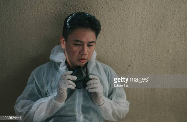 an asian chinese mid adult man resting and taking off protective wear after disinfection process, exhausted with marks on his face