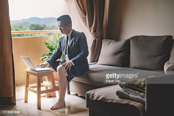 an asian chinese mid adult man with tie and suit and short pant sitting on sofa using laptop in his living room for video conference with his business partner and colleague virtual business meeting - audience free event stock pictures, royalty-free photos & images