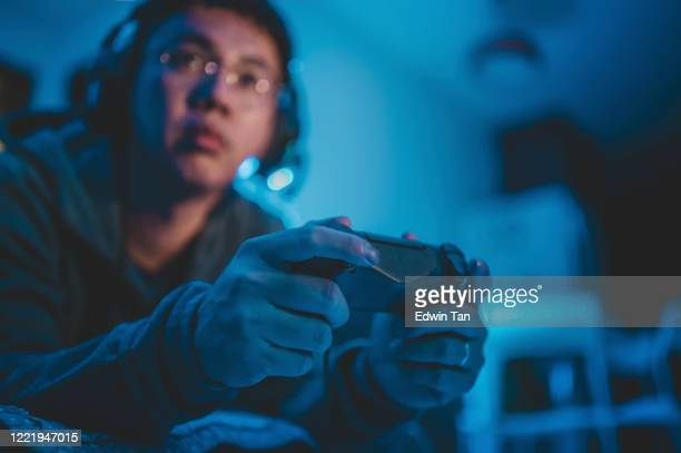 an asian chinese mid adult playing video games at home alone at night in darkness with headset and game controller sitting on sofa lying down