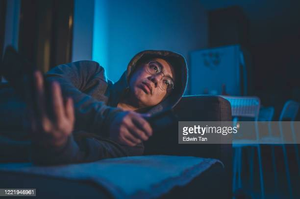 an asian chinese mid adult watching tv at home alone at night in darkness leaning on sofa - couch potato stock pictures, royalty-free photos & images