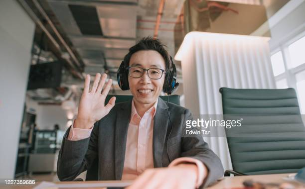 an asian chinese mid adult white collar worker talking to the camera video calling video conference with his business partners  with face mask - instructor stock pictures, royalty-free photos & images