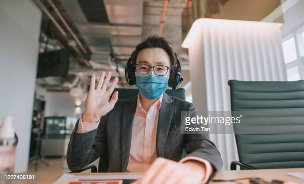 an asian chinese mid adult white collar worker talking to the camera video calling video conference with his business partners with face mask