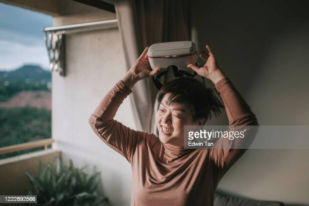 an asian chinese mid adult woman playing games enjoying vr virtual reality online using vr google in living room - google stock pictures, royalty-free photos & images