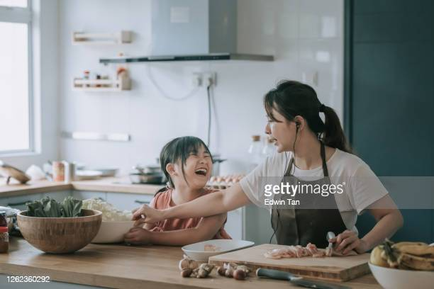 an asian chinese mother cooking preparing food at kitchen counter  with her daughter - asia stock pictures, royalty-free photos & images