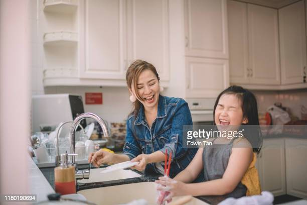 an asian chinese mother washing dishes with her daughter in the kitchen and having fun time bonding - family with one child stock pictures, royalty-free photos & images