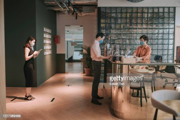 an asian chinese receptionist conducting standard operating procedure for illness prevention by measuring visitors colleague coworkers body temperature and record their personal data - new normal stock pictures, royalty-free photos & images