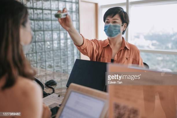 uma recepcionista chinesa asiática que conduz o procedimento operacional padrão para a prevenção de doenças medindo a temperatura corporal dos colegas colegas de visitantes e registrando seus dados pessoais - instruções - fotografias e filmes do acervo