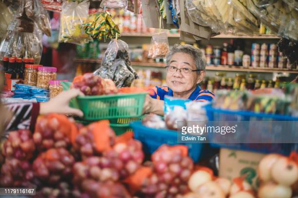 an asian chinese senior man as owner of the spice store receiving basket of products from his customer for price calculation at the spice stall - banca de mercado imagens e fotografias de stock