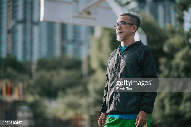an asian chinese senior man coach in the morning wearing windbreaker at basketball court getting ready to practice and exercising - windbreak stock pictures, royalty-free photos & images
