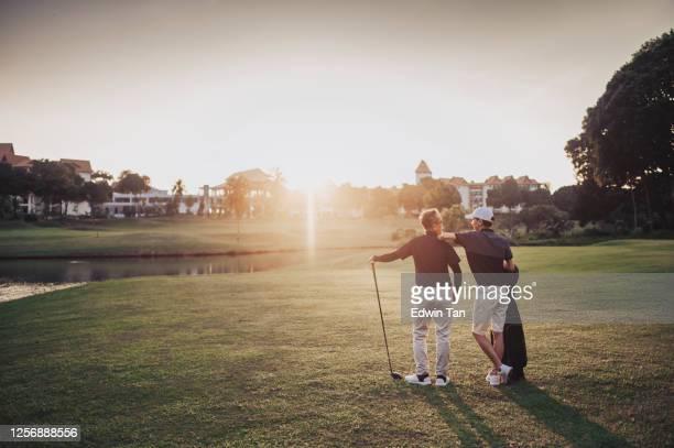 un golfista asiatico cinese senior portando il suo golf club sulla spalla e guardando la vista nel campo da golf - golf foto e immagini stock