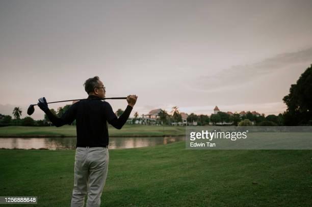 アジアの中国人の先輩ゴルファーが彼の肩に彼のゴルフクラブを運び、ゴルフコースで景色を見て - ゴルフクラブ ドライバー ストックフォトと画像
