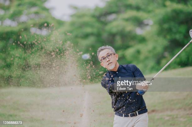 an asian chinese senior man golfer hitting his golf ball in a sand trap with his iron club - effort stock pictures, royalty-free photos & images