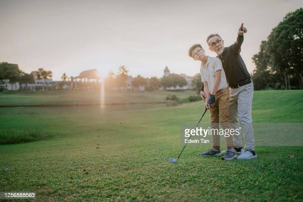 an asian chinese senior man golfer teaching his grandson how to play golf at golf course during sunset