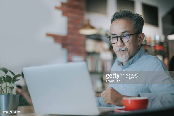 an asian chinese senior man having discussion with his colleague via online virtual meeting in a cafe - only men stock pictures, royalty-free photos & images