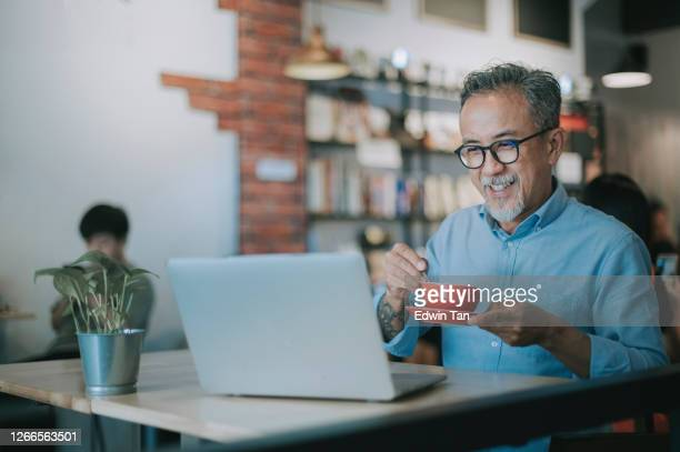 an asian chinese senior man having discussion with his colleague via online virtual meeting in a cafe - asia stock pictures, royalty-free photos & images