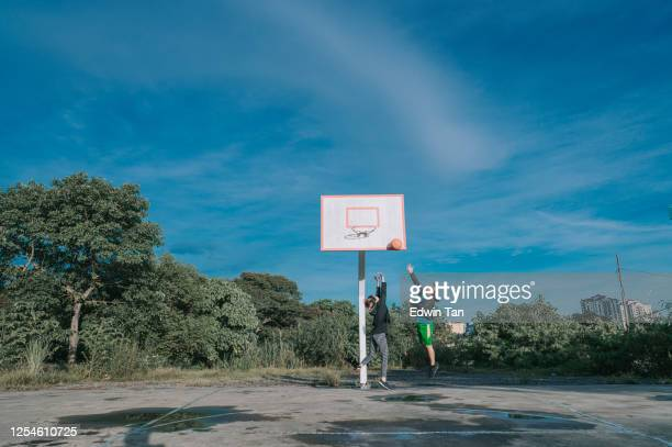 an asian chinese senior man practicing basket ball game in the basket ball court in the morning with his daughter - match sport stock pictures, royalty-free photos & images